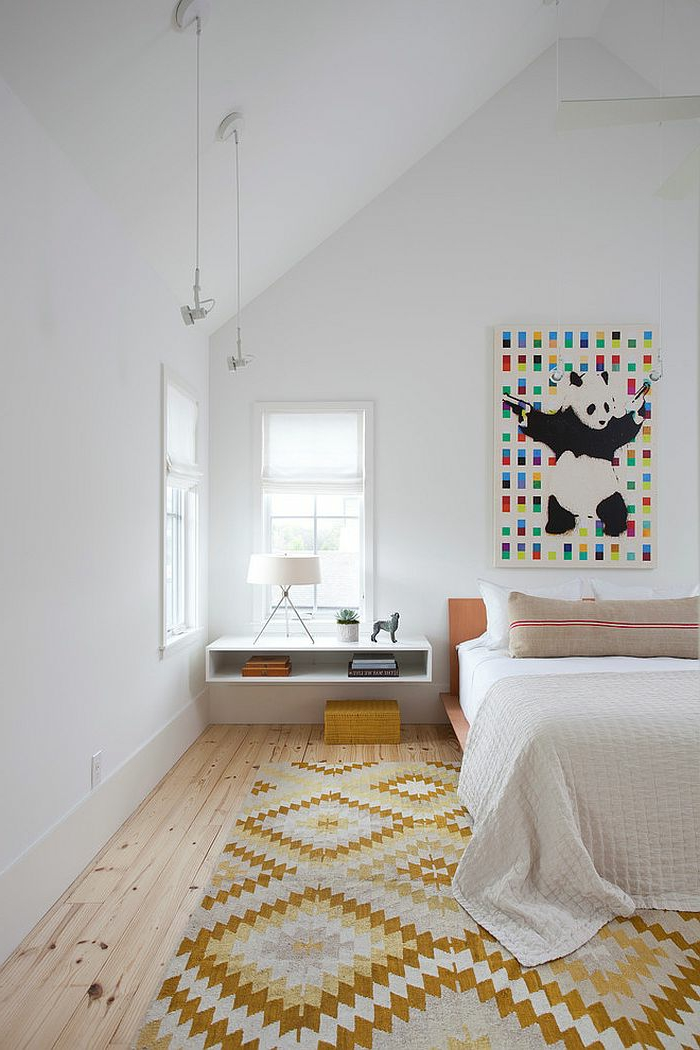 skandinavisches Schlafzimmer mit Schrägdach, weißen Wänden und weiße Zimmerdecke, Teenager-Schlafzimmer mit Holzboden, Musterteppich in Gelb und Weiß, weißer Wandregal mit einer Leselampe, eine Pferdenfigur und zwei Haufen Bücher darauf, großes Leinwandbild mit einem Panda mit zwei Pistolen