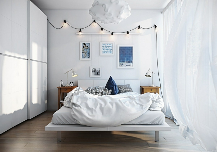 riesiger Kleiderschrank mit Schiebetüren, Laminatboden in heller Farbe, zwei hölterne Nachttische mit zwei Lampen, Wandbilder mit Sprüchen, zwei Kissen mit Musterbezügen und ein Kissen mit blauem Bezug, Lichterkette aus Glühbirnen, Kronleuchter mit Wolken-Optik, lange weiße Gardinen bis zum Boden