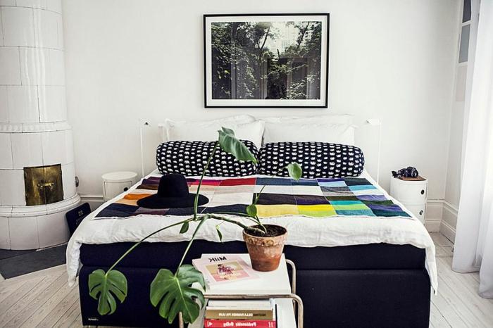 kleiner Kamin in der linken Ecke des Zimmers, großes Bild über dem Bett, runde Kissen mit schwarz-weißen Bezügen, bunte Bettdecke mit quadratischem Muster, weißer Tisch mit Metallbeinen, grüne Pflanze in einem Keramiktopf
