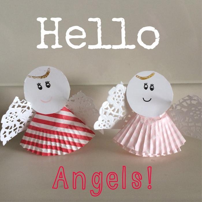 zwei kleine diy engel mit weißen flügeln aus papier und mit schwarzen augen - engel basteln mit kindern