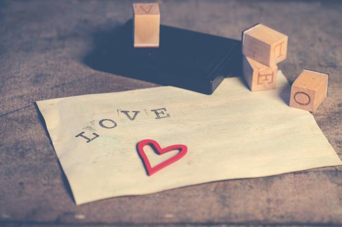 eine romantische Botschaft -Bilder zum Valentinstag ein Zettel mit der Aufschrift Liebe und ein Herzchen