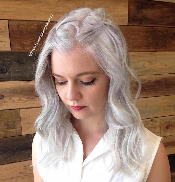 Haarfarbe Silberblond - ein junges Mädchen mit lässiger Frisur, das Mädchen hat eine weiße Bluse an