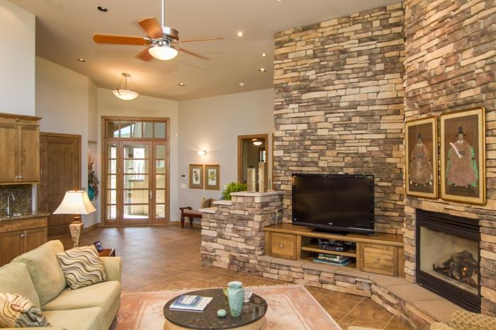 ein kompaktes Wohnzimmer mit Kamin, Fernseher auf einem Regal, Steinwand Wohnzimmer