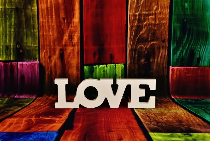 das Wort Liebe mit weißen Buchstaben geschrieben, Bilder zum Valentinstag, buntes Holz als Hintergrund