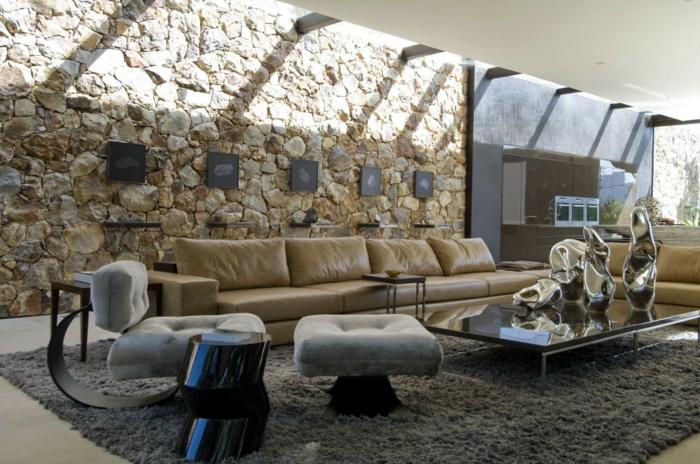 ein geräumiges Wohnzimmer, eine niedrige Couchtisch, Natursteinwand, ein langes Sofa