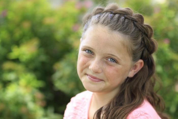 Mädchenfrisuren - ein niedliches Mädchen mit braunem Haar und blauen Augen, Zopf wie Krone