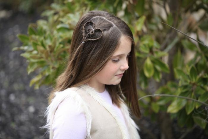 Mädchenfrisuren - ein niedliches Mädchen mit einem Herzchen in Haaren