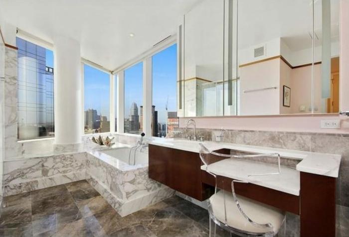 Badraum mit großem Eckfenster, runde Säule mit dekorativer Funtion, Wand mit braunen Simsen, Schminktisch mit Plastikstuhl mit Polstersitz
