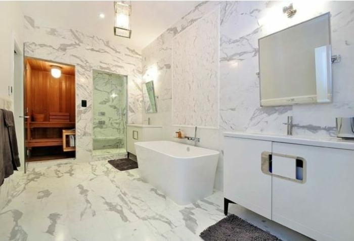 Sauna im eigenen Bad, Duschkabine mit Glastür, Fußmatte vor dem Waschbecken, Waschbeckenschrank mit Lochgriffen