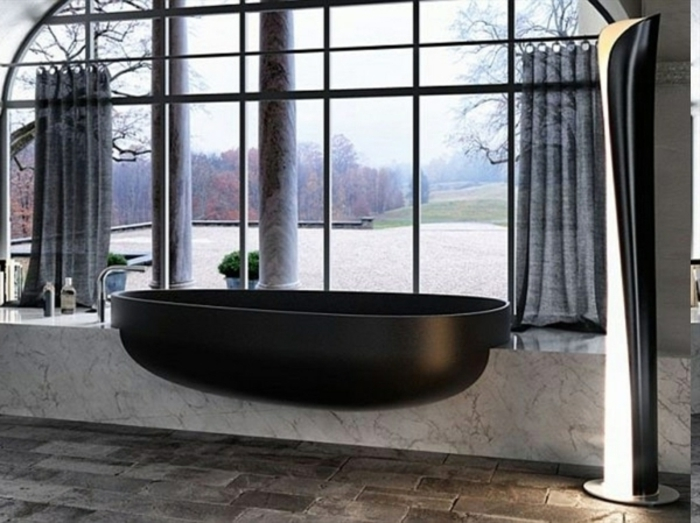 Natursteinwanne vor dem großen Fenster, lange halbdurchsichtige Gardinen in grauer Farbe, Designer-LED-Lampe