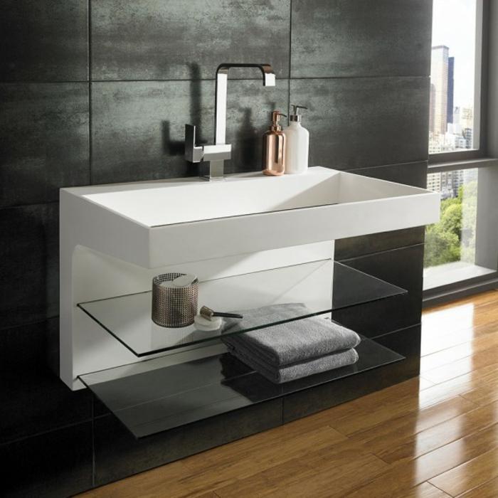 Wandverkleidung aus grauen Wandpaneelen, Wandregale aus Glas, graue Badetücher auf dem Glasregal, zwei Seifenbehälter für Handseife