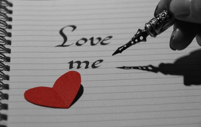 mit einem Füller Liebe mich mit Ornamenten geschrieben - Bilder zum Valentinstag und ein kleines rotes Herzchen aus Papier