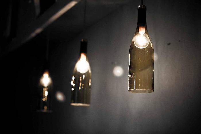 flaschenlampe selber bauen - eine schwarze wand und drei grüne flaschenlampen