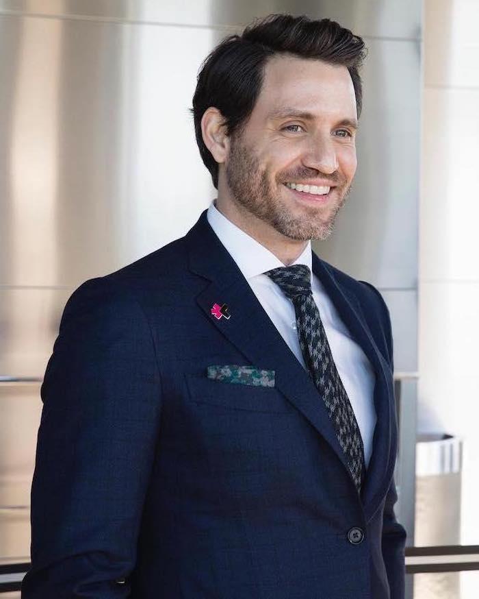 Sechs-Tage-Bart und mittellange Haarfrisur, eleganter Anzug mit weißem Hemd und Krawatte