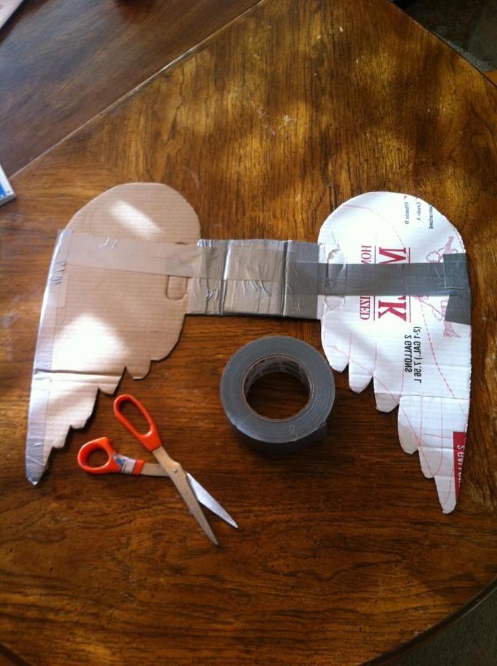 ein tisch aus holz - eine rote schere und zwei weiße diy engelsflügel aus papier - engel aus papier basteln