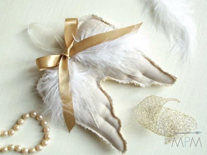 zwei weiße engelsflügel mit einer gelben schleife und weißen federn und kette - engel basteln