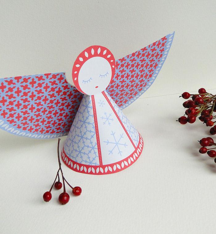 engel mit blauen augen und roten flügeln und großen schneeflocken - bild mit einem engel aus papier und kleinen roten früchten