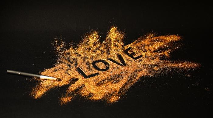 ein Maler arrangiert Liebesbilder für Sie, mit einem Farbstoff auf Pulver schreibt er Liebe