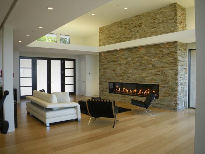 eine Wandverkleidung Steinoptik, ein warmer Kamin, Laminatboden, dezente Wohnzimmermöbel