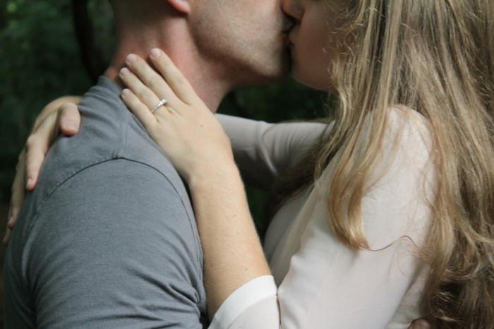 Verliebte Bilder - beide Verliebte küssen sich, nachdem Sie einen Verlobungsring bekommen hat