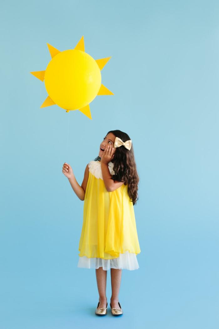 Sonne Kostüm von einem kleinen Mädchen mit gelben Kleid, das Mädchen trägt einen gelben Ballon