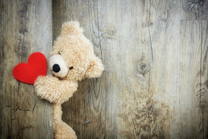 Kuschelbilder - ein kuscheliger Teddybär mit einer Valentinstagkarte in der Hand