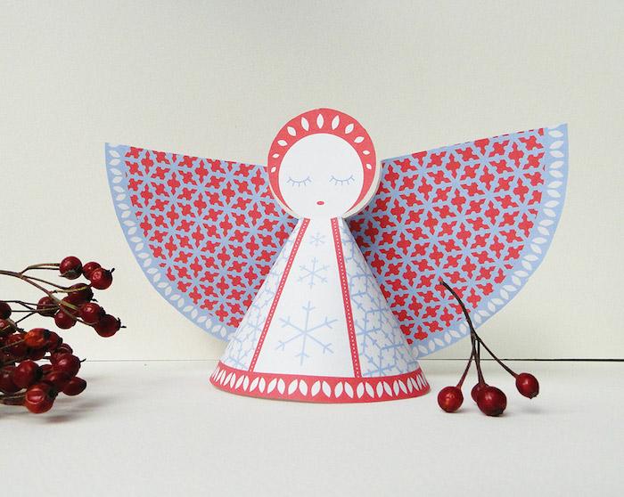 bild mit kleinen roten früchten und mit einem weißen engel mit roten flügeln aus papier und mit kleinen und großen blauen schneeflocken