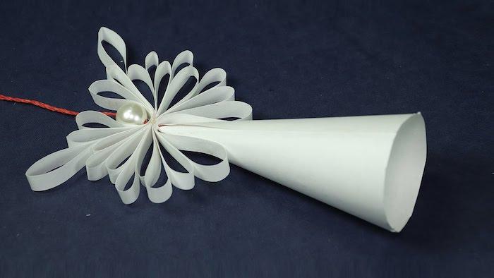 ein blauer tisch und ein weißer engel mit flügeln mit weißen federn - engel aus papier basteln