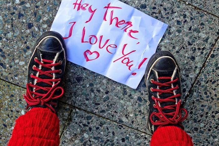 Valentinstagsgrüße - das Mädchen sieht zufällig nieder und sieht ein Zettel mit Liebeserklärung