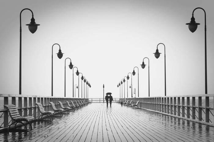 schwarz-weißes Foto von zwei Verliebte, Grüße zum Valentinstag, über eine Brücke gehen
