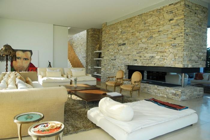 Einzimmerwohnung, Wohnraum mit Natursteinwand als Raumteiler, eine Matratze für Gäste