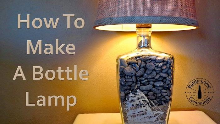 kleiner tisch mit einem großen schlafzimmer lampe mit einer durchsichtigen flasche und vielen kleinen grauen steinen