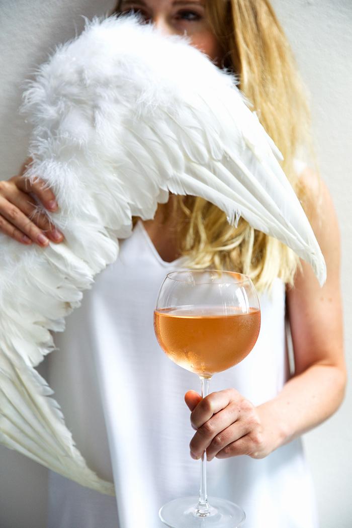 eine junge frau mit zwei weißen engelsflügeln mit weißen federn und ein glas wein