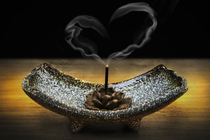 Kerzenständer mit einem Lotos in der Mitte mit einer Duftkerze, deren Rauch ein Herzchen formt - Grüße zum Valentinstag
