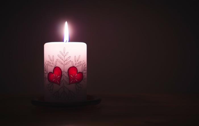 eine seltsame weiße Kerze mit Blumenmuster und Herzen versehen - Grüße zum Valentinstag