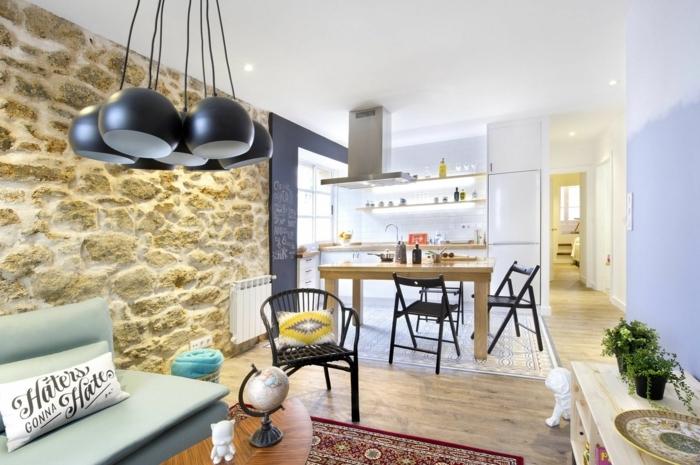 Wohnzimmer mit Naturstein Verblender an einer der Wände, runde Lampen, blaues Sofa, weißes Kissen