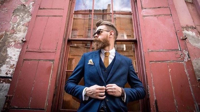 Hipster Bart Inspiration, schicker dunkelblauer Anzug mit weißem Hemd und hellbrauner Krawatte