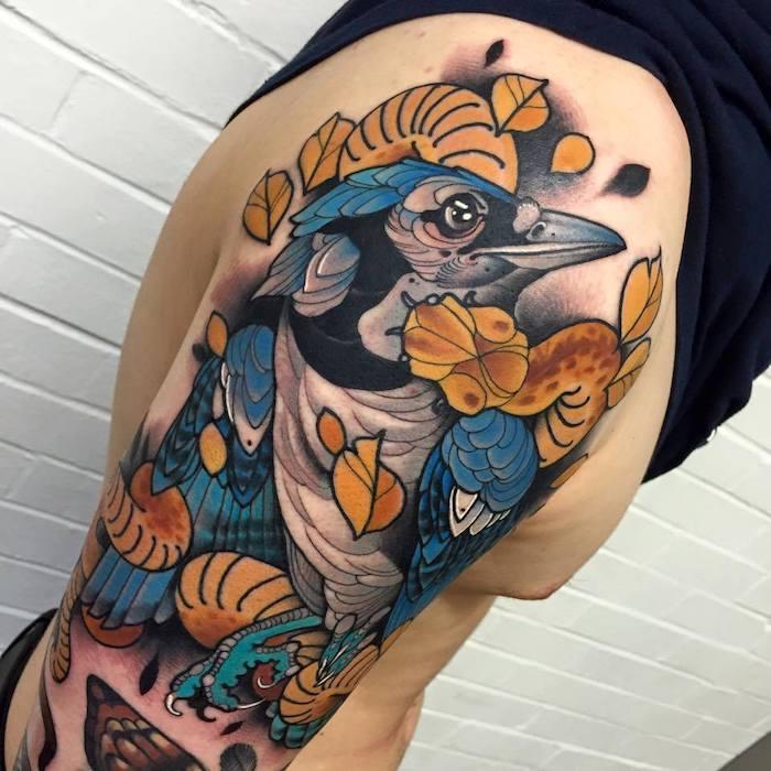 großes farbiges raben tattoo am oberarm, blauer rabe mit fallenden herbstblättern