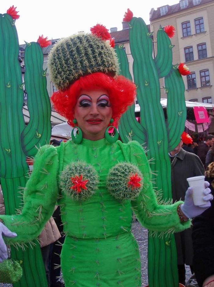 eine Frau verkleidet wie einen Kaktus in einem grünen Kostüm mit einer roten Perüke