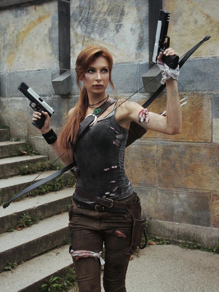 Lara Croft Tomb Raider Kostüm aus braunen zerrissenen Hosen mit zwei Ledergürteln und einem grauen zerrissenen Top mit Spaghetti-Trägern