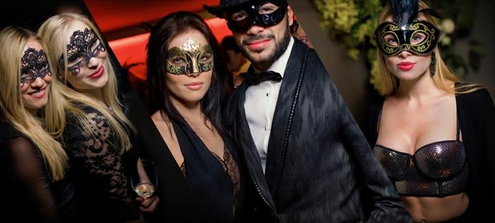 moderne Gatsby Karneval-Kostüme für Frauen und Männer - zwei blonde Frauen mit schwarzen Spitzenkleidern und Augenmasken, Mann mit schwarzem Sakko weißem Hemd und schwarzer Fliege, Blondine mit bauchfreiem Pailleten-Top und schwarzer Jacke