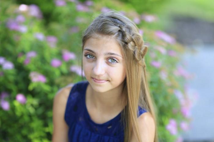 Kinderfrisuren - ein Mädchen mit Zopf beiseite trägt ein blaues Kleid