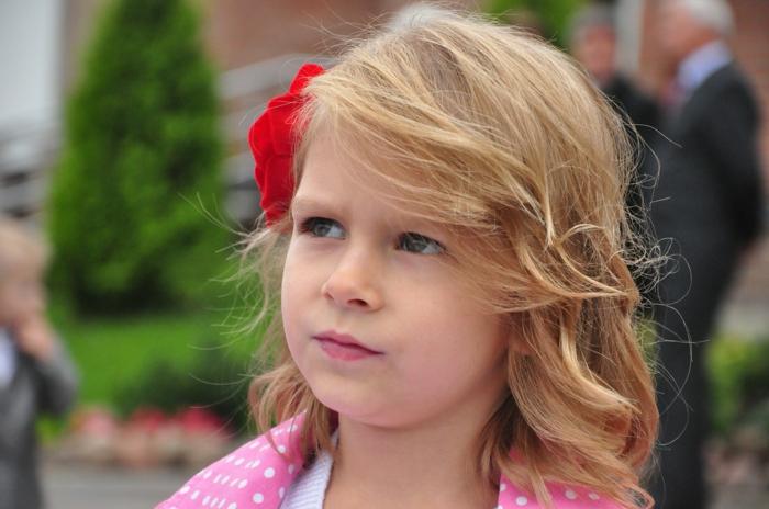 Kinderfrisuren - ein blondes Mädchen mit lässiger Frisur, eine rote Schleife