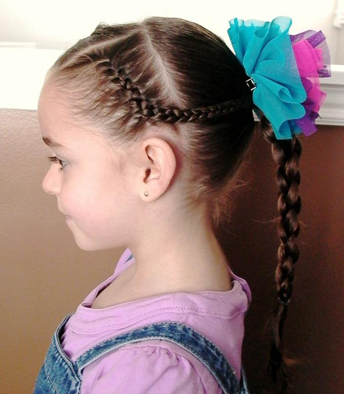 Kinderfrisuren - ein Mädchen mit langen Haaren, die geflochten sind, zwei Schleifen