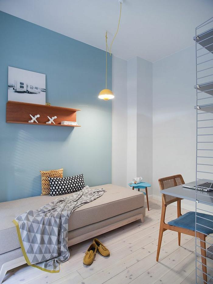 hellblaue Wand mit Holzregal, hängende Lampe mit gelbem Lampenschirm, schmales Bett mit Plastikbeinen, Schlafdecke mit Triangel-Print, zwei kleine dekorative Kissen mit Print, kleiner blauer Beistelltisch, alter Holzstuhl mit blauem Polstersitz, grauer Schreibtisch mit Metall-Regalen, ein Paar gelbe Veloursschuhe