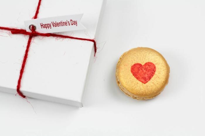 Französische Macarons mit roten Herzen zum Valentinstag schenken, mit Geschenkpapier verpackt
