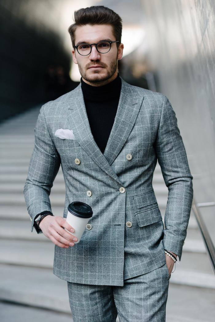männer anzug in grauer farbe kariert und zwei reihen von knöpfen schwarzes poloshirt lesebrille kaffee trinken auf dem weg