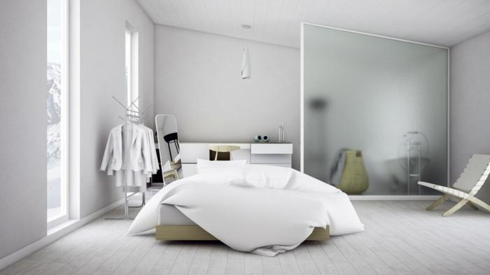 weiß eingerichtetes Schlafzimmer mit Holzboden, Doppelbett mit weißer Bettwäsche, zwei schmale Fenster bis zum Boden, Hänger mit weißen Kleidern, weiße Kommode hinter dem Bett, schmaler Spiegel auf der linken Seite, Glasraumteiler für Schrägdach-Zimmer