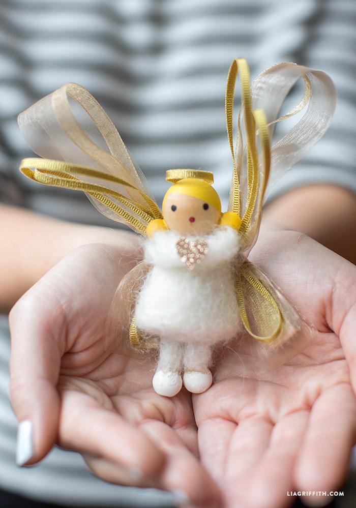 ein kleiner weißer engel mit zwei goldenen flügeln und einem kleinenweißen kleid