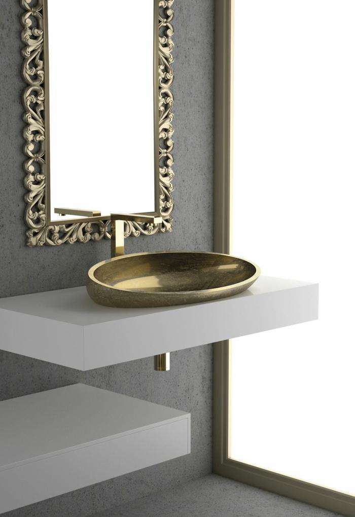 kleines Waschbecken mit Goldüberzug, modernes Badezimmerdesign inspiriert von der Antike, schmaler Spiegel mit vergoldetem Rahmen mit vielen Ornamenten, Bad-Raumteiler aus Glas